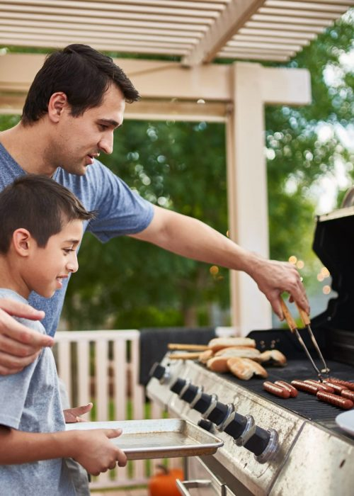 father and son outdoor barbecue with propane tank
